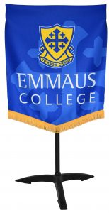Music stand banner on a music stand. The banner has a blue background and yellow fringe. A school crest is displayed on the banner.